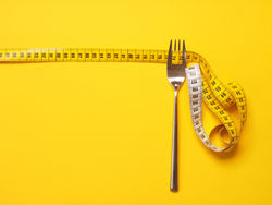 stock-photo-fork-with-a-measuring-tape-diet-or-healthy-eating-concept-1061082680