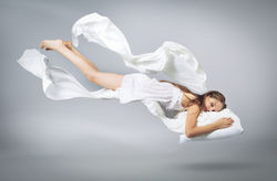 stock-photo-sleeping-girl-flying-in-a-dream-white-linen-flying-through-the-air-light-grey-background-1010662003.jpg