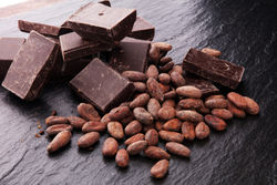 stock-photo-dark-chocolate-pieces-stacks-and-cocoa-beans-culinary-background-767919487.jpg